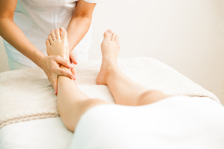 60090948 - closeup of a female therapist giving a foot massage to a client at a health and beauty spa